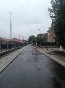 Het eerste deel van de N8 tot de d'Arconatistraat heeft al een asfaltlaag. Nu de voetpaden...